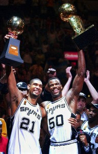 San Antonio Spurs players Tim Duncan (21) holds his MVP trophy while teammate David Robinson (50) holds the championship trophy after the Spurs beat the New Jersey Nets 88-77 to win the NBA Championship in Game 6 of the NBA Finals in San Antonio, June 15, 2003. The sports year in Texas got off to a rousing start with Bill Parcells saying on Jan. 1 that he had agreed to coach the Dallas Cowboys and soon after, the San Antonio Spurs gave David Robinson the ultimate reitrement present, an NBA title. (AP Photo/Eric Gay, file)